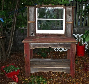 A great looking potting bench with shelves and a re-purposed window.