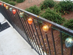 A colorful style of patio string lights along a railing.